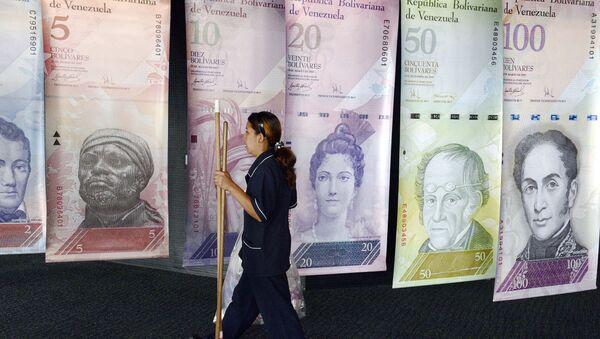 A woman walks past banners portraying the Venezuelan currency, the Bolivar, at the Venezuelan Central Bank in Caracas  - Sputnik International