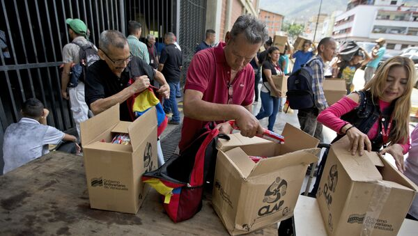 In this July 6, 2018 photo, employees of a government-supported cultural center collect their boxes with subsided food distributed under government program named CLAP in downtown Caracas, Venezuela. Everyone from museum curators to janitors waited in line to sign a clipboard before government loyalists hand over the box of food. - Sputnik International