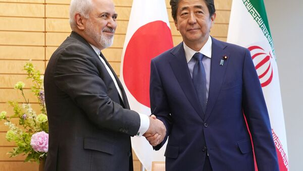 Iranian Foreign Minister Mohammad Javad Zarif, left, and Japanese Prime Minister Shinzo Abe, right, shake hands at Abe's official residence in Tokyo Thursday, May 16, 2019 - Sputnik International
