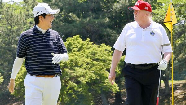 U.S. President Donald Trump talks with Japanese Prime Minister Shinzo Abe as they play golf at Mobara Country Club in Mobara, Chiba prefecture, Japan, in this photo released by Japan's Cabinet Public Relations Office via Kyodo May 26, 2019 - Sputnik International