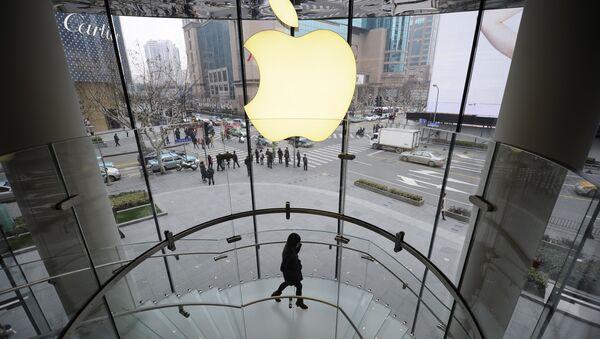 A customer walks under an Apple logo sign at an Apple shop in Shanghai on February 22, 2012 - Sputnik International