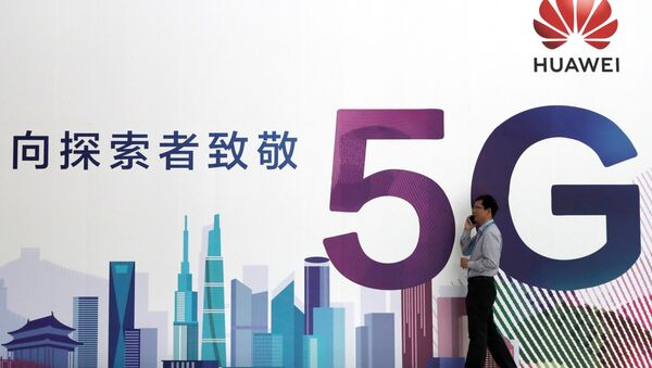 A man talks on his mobile phone beside Huawei's billboard featuring 5G technology at the PT Expo in Beijing, China, September 26, 2018 - Sputnik International