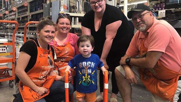 Toddler and his family pose with Home Depot workers who donated and assembled the two-year-old's PVC walker - Sputnik International