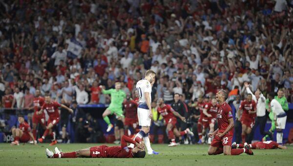 Tottenham's Harry Kane walks past Liverpool's players as they celebrate after winning the Champions League final soccer match against Tottenham Hotspur at the Wanda Metropolitano Stadium in Madrid, Saturday, June 1, 2019. - Sputnik International