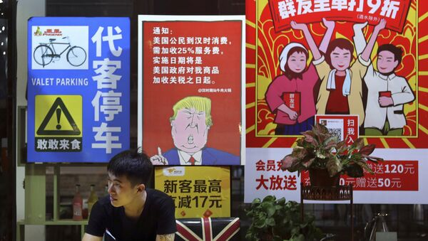 A man stands near a poster depicting a mural of U.S. President Donald Trump stating that all American costumers will be charged 25 percent more than others starting from the day president Trump started the trade war against China, on display outside a restaurant in Guangzhou in south China's Guangdong province.  - Sputnik International