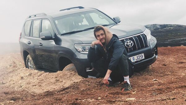 Alexander Tikhomirov, a Russian lifestyle blogger, poses near the off-roader stuck in clay - Sputnik International