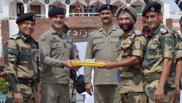 Pakistani Wing Commander Bilal (C) presents sweets to Indian Border Security Force (BSF) Deputy Inspector General JS Oberoi (2R) on the occasion of the Eid al-Fitr festival which marks the end of the holy month of Ramadan, at the India Pakistan Wagah Border Post, about 35 kms from Amritsar on July 6, 2016 - Sputnik International