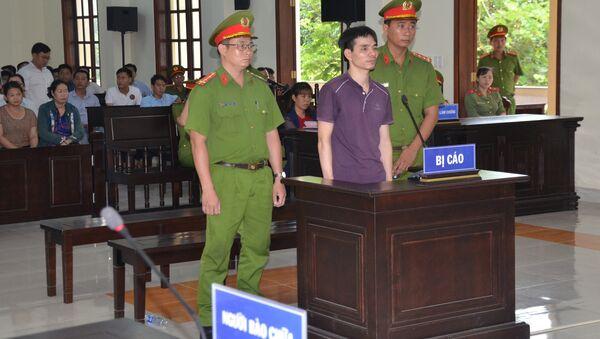 Vietnamese Facebook user Nguyen Ngoc Anh stands between policemen during his trial at a court in Ben Tre province - Sputnik International