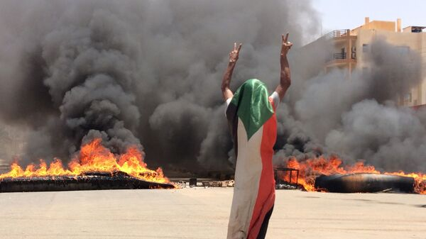 A protester wearing a Sudanese flag flashes the victory sign in front of burning tires and debris on road 60, near Khartoum's army headquarters. - Sputnik International