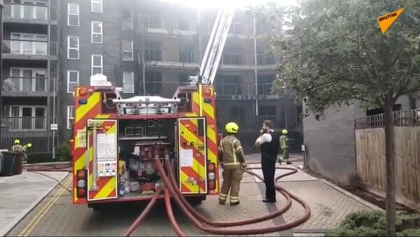 Dozens of firefighters were called to the scene on Sunday as a fire broke out at a new apartment block in the east of the British capital - Sputnik International