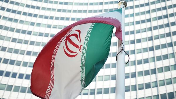 An Iranian flag waves in a wind outside the Vienna International Centre hosting the United Nations (UN) headquarters and the International Atomic Energy Agency (IAEA) as the socalled EU 5+1 talks with Iran take place in Vienna, on July 3, 2014 - Sputnik International