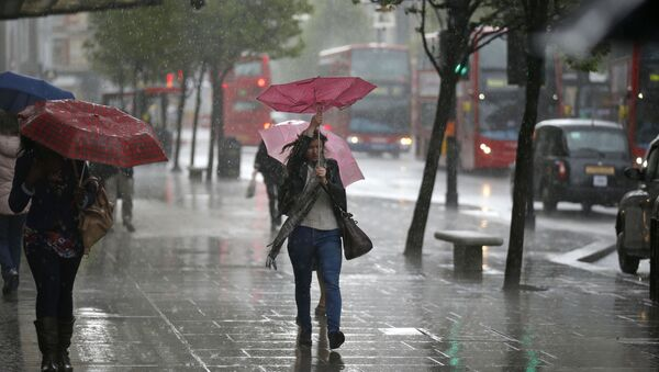 A woman's umbrella blown inside-out as she walks through a heavy rain shower on Oxford Street in London (File) - Sputnik International