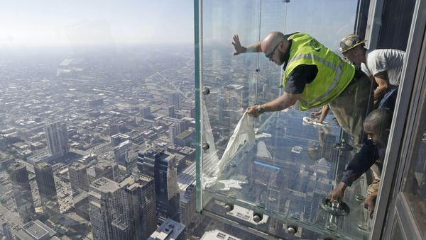 Glaziers from MTH Industries finish replacing a layer of protective coating over the glass surface on the floor of one of four transparent ledges that jut out from the 103rd floor of the Willis Tower in Chicago on Thursday, May 29, 2014. The see-through glass bays known as The Ledge were designed with a protective coating that completely covers all glass surfaces to protect against scratches. One of the coatings cracked Wednesday night when a family was standing on it. Officials say the family wasn't in danger and the coating does not affect the structural integrity of the enclosure. - Sputnik International