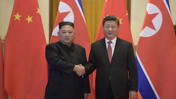 In this Tuesday, Jan. 8, 2019, photo released by China's Xinhua News Agency, North Korean leader Kim Jong Un, left, and Chinese President Xi Jinping shake hands as they pose for a photo before talks at the Great Hall of the People in Beijing - Sputnik International