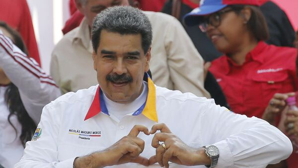 In this 20 May 2019 photo, Venezuela's President Nicolas Maduro flashes a hand-heart symbol to supporters outside Miraflores presidential palace in Caracas, Venezuela. - Sputnik International