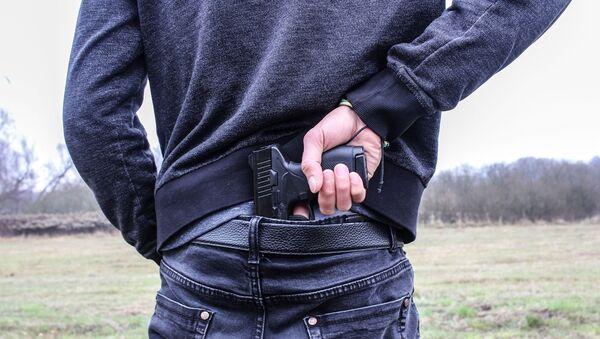 Man pulls handgun from waistband - Sputnik International
