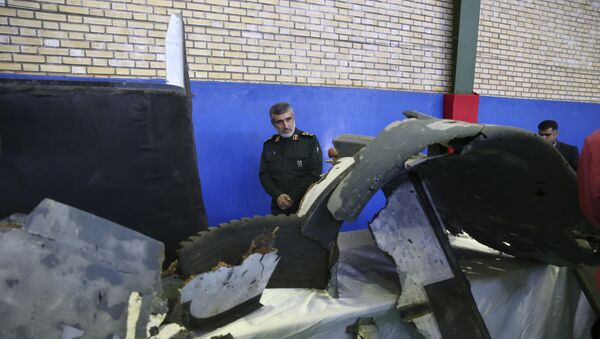 Head of the Revolutionary Guard's aerospace division Gen. Amir Ali Hajizadeh looks at debris from what the division describes as the U.S. drone which was shot down on Thursday, in Tehran, Iran, Friday, June 21, 2019 - Sputnik International