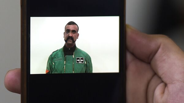 A Pakistani man watches the latest video statement released by Pakistan's military authorities of the Indian Wing Commander pilot Abhinandan Varthaman on his smartphone in Islamabad on March 1, 2019. - An Indian pilot shot down in a dogfight with Pakistani aircraft returned to India on March 1, after being freed in what Islamabad called a peace gesture following the two countries' biggest standoff in years. (Photo by AAMIR QURESHI / AFP) - Sputnik International