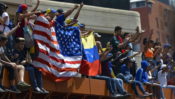 Anti-government protesters hold the US national flag next to a Venezuelan national flag during the commemoration of May Day in Caracas, on May 1, 2019 after a day of violent clashes on the streets of the capital spurred by Venezuela's opposition leader Juan Guaido's call on the military to rise up against President Nicolas Maduro - Sputnik International