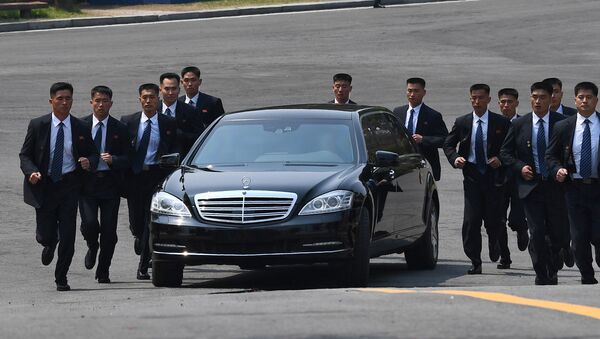 North Korean bodyguards jog next to a car carrying North Korea's leader Kim Jong Un returning to the North for a lunch break after a morning session of the inter-Korean summit at the truce village of Panmunjom on April 27, 2018 - Sputnik International