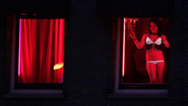 In this photo taken Monday Jan. 10, 2011 a prostitute advertises her wares behind red-lit windows in Amsterdam, Netherlands - Sputnik International