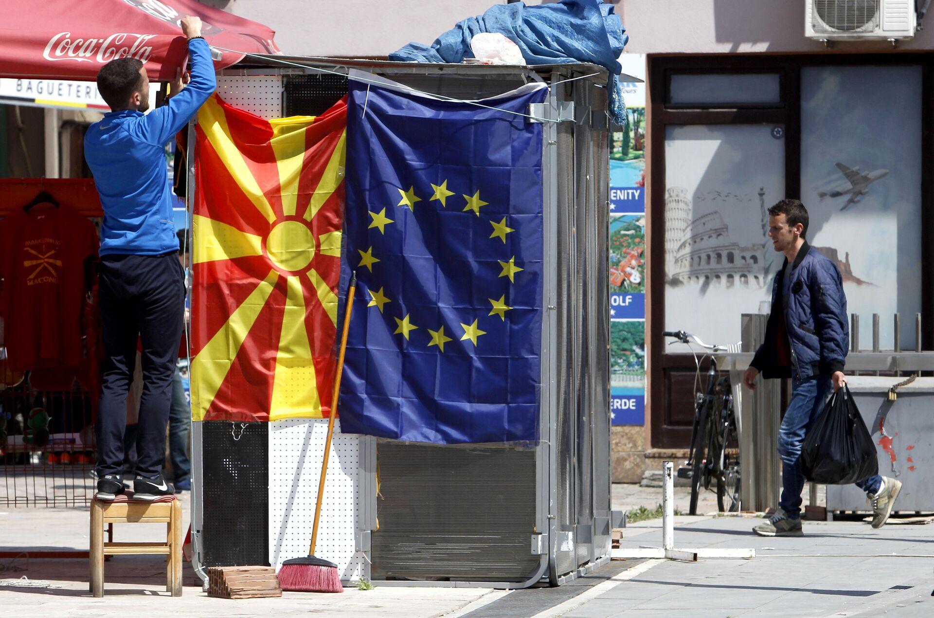 A street vendor fixes a North Macedonia flag next to an EU flag in a street in Skopje - Sputnik International, 1920, 07.09.2021