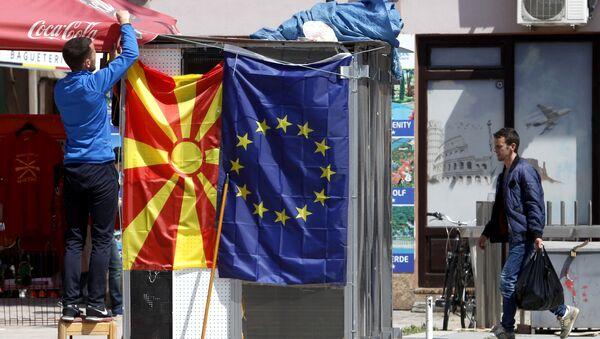 A street vendor fixes a North Macedonia flag next to an EU flag in a street in Skopje - Sputnik International