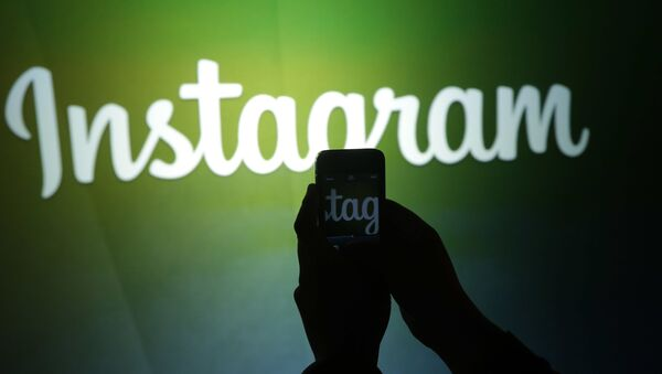 A journalist makes a video of the Instagram logo using the new video feature at Facebook headquarters in Menlo Park, Calif., Thursday, June 20, 2013 - Sputnik International