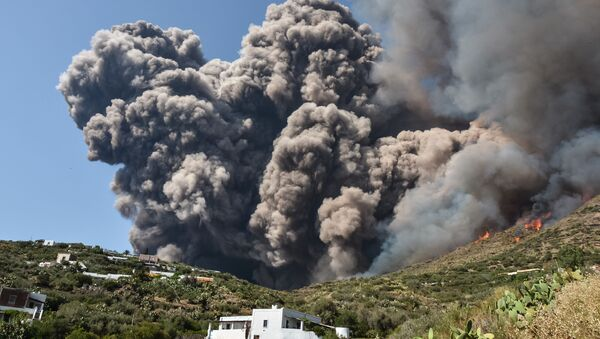 Smoke billows and flames propaqate accross the hillside neqr houses after the Stromboli volcano erupted on July 3, 2019 on the Stromboli island, north of Sicily - Sputnik International