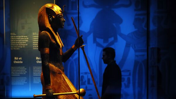A visitor walks by a wooden guardian statue of the Ka of the king wearing the Names Headcloth displayed as part of 'Tutankhamun, the treasure of the Pharaoh', an exhibition in partnership with the Grand Egyptian Museum at the Grande Halle of La Villette in Paris, France, Thursday, March 21, 2019.  - Sputnik International