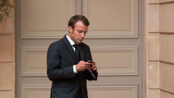 Emmanuel Macron, looks at his phone - Sputnik International