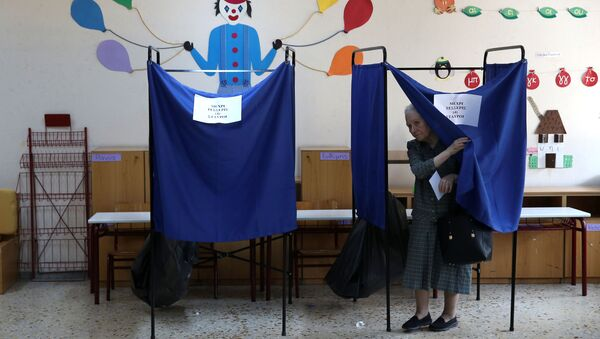 A woman leaves a voting booth to cast her ballot for the general election in Athens, Greece, July 7, 2019. - Sputnik International