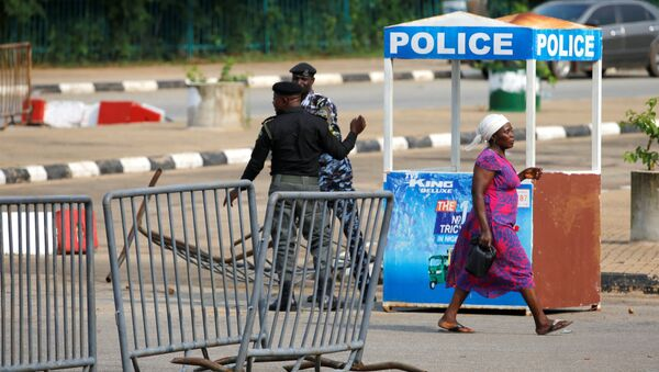 A woman walks past police officers outside the National Assembly in Abuja - Sputnik International