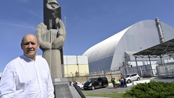 French Foreign Minister Jean-Yves Le Drian stands next to the monument in memory of the victims of the Chernobyl nuclear disaster at the New Safe Confinement (NSC) movable enclosure at the nuclear power plant in Chernobyl, Ukraine, Saturday, June 1, 2019. - Sputnik International