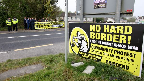 Protesters against Brexit and the possible imposition of any hard border between Northern Ireland and Ireland  gather with a banner at the border (marked where the tarmac changes and the lines change between white and yellow) between Derry (Londonderry) in Northern Ireland and County Donegal in the Republic of Ireland near the Irish village of Bridge End on April 18, 2019 - Sputnik International