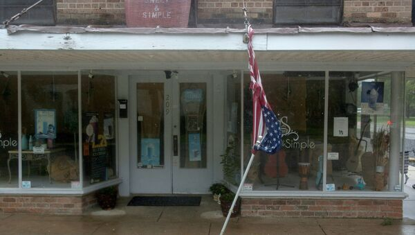 A torn U.S. Flag dangles from a store front in Morgan City, Louisiana ahead of Tropical Storm Barry Saturday, July 13,2019. - Tropical Storm Barry is the first tropical storm system of 2019 to make landfall in the United States and could dump up to two feet of rain along with strong winds and storm-surge flooding according to weather reports. (Photo by Seth HERALD / AFP) - Sputnik International