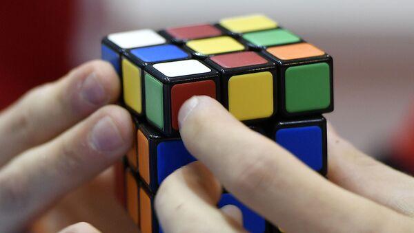 A gamer plays with Rubik's Magic Cube at the international game fair 'SPIEL' in Essen, Germany, Thursday, Oct. 26, 2017. - Sputnik International