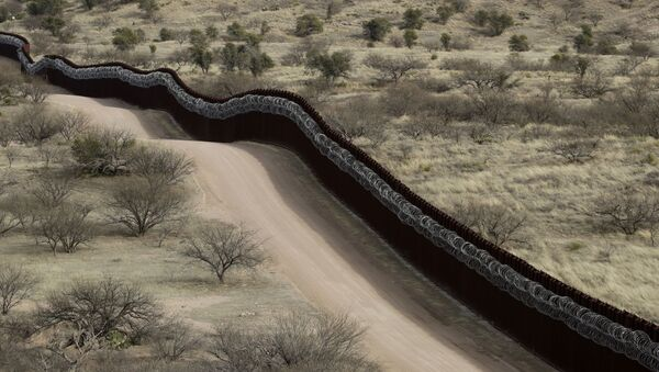 In this March 2, 2019 file photo, a razor-wire-covered border wall separates the United States, at left, from Mexico east of Nogales, Ariz - Sputnik International