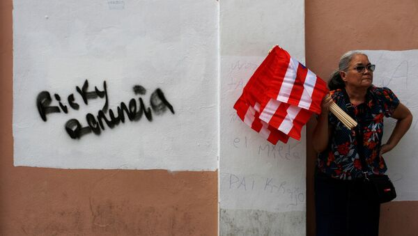 A woman sells Puerto Rican flags next to a graffiti that reads Ricky resign during the seventh day of protest calling for the resignation of Governor Ricardo Rossello in San Juan, Puerto Rico July 19, 2019. - Sputnik International