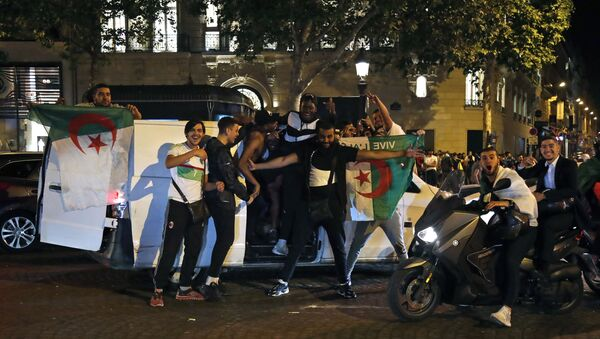 Algeria's supporters celebrate with the Algerian national flag in the Champs Elysee Avenue in Paris, after Algeria won 1-0 the 2019 Africa Cup of Nations (CAN) final football match between Algeria and Senegal, on July 19, 2019 - Sputnik International