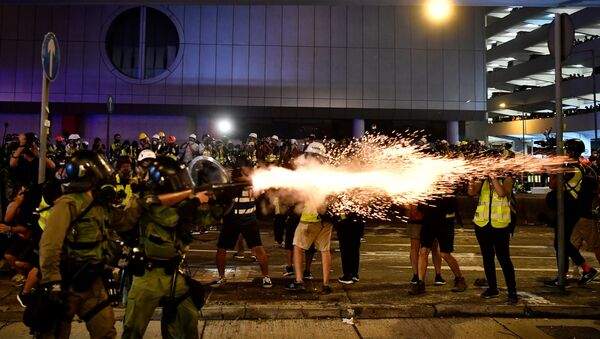 A policeman fires tear gas at protesters to disperse them after a march against a controversial extradition bill in Hong Kong on July 21, 2019.  - Sputnik International