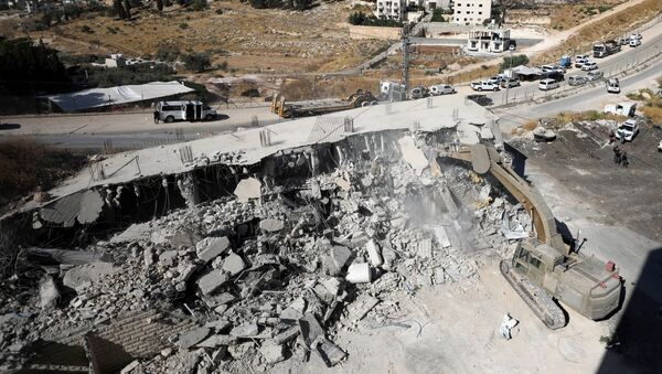 An Israeli military bulldozer demolishes a building near a military barrier in Sur Baher, a Palestinian village on the edge of East Jerusalem in an area that Israel captured and occupied in the 1967 Middle East War July 22, 2019 - Sputnik International