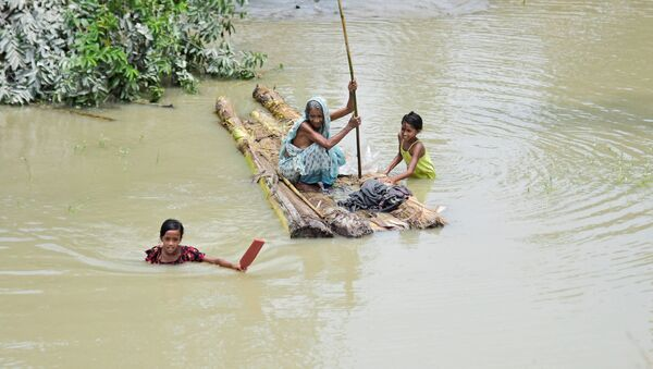 A woman rows a makeshift raft as girls wade through flood waters at the Laharighat village in Morigaon district, in the northeastern state of Assam, India, July 21, 2019 - Sputnik International