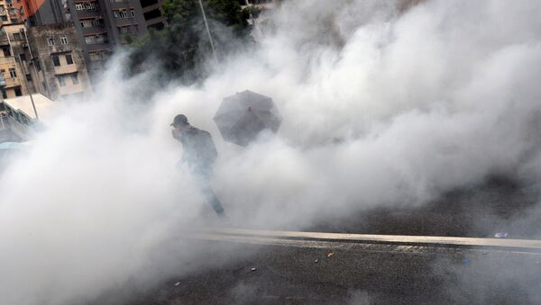 A demonstrator is seen amidst smoke from tear gas during a protest against the Yuen Long attacks in Yuen Long - Sputnik International