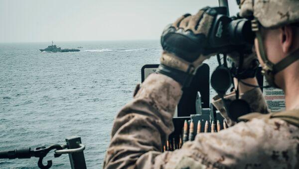 A U.S. Marine observes an Iranian fast attack craft from USS John P. Murtha during a Strait of Hormuz transit, Arabian Sea off Oman - Sputnik International
