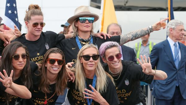 Members of the US Women's National Soccer Team pose with the trophy at Newark Liberty International Airport after winning the 2019 Women's World Cup. - Sputnik International
