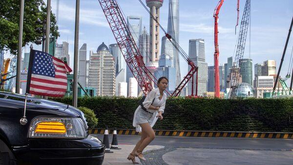 A woman sprints past a U.S. embassy car outside a hotel in Shanghai Tuesday, July 30, 2019  - Sputnik International