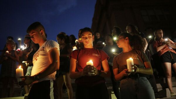 Samuel Lerma, Arzetta Hodges and Desiree Qunitana join mourners taking in a vigil at El Paso High School after a mass shooting at a Walmart store in El Paso, Texas, U.S. August 3, 2019 - Sputnik International