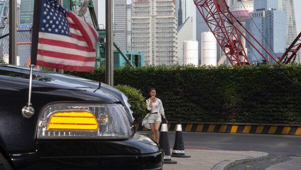 A woman walks towards a U.S. embassy car outside a hotel in Shanghai on Tuesday, July 30, 2019 - Sputnik International