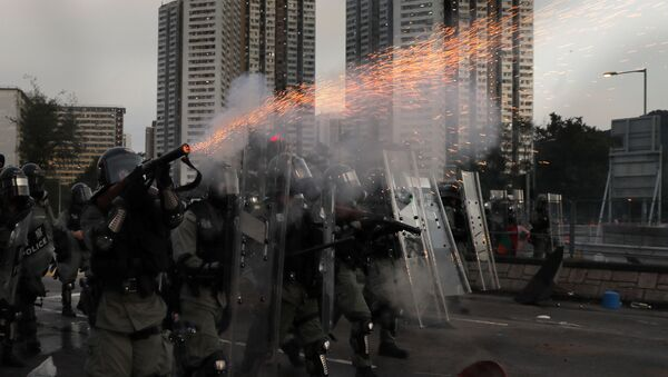 A riot police fires tear gas during a confrontation with protesters on Monday, Aug. 5, 2019. Droves of protesters filled public parks and squares in several Hong Kong districts on Monday in a general strike staged on a weekday to draw more attention to their demands that the semi-autonomous Chinese city's leader resign. - Sputnik International